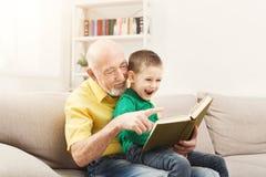 Livre de lecture d'homme supérieur pour son petit-enfant Photographie stock