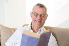 Livre de lecture d'homme supérieur sur le sofa Photographie stock libre de droits