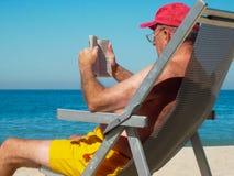 Livre de lecture d'homme sur la plage Photo stock