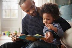 Livre de lecture d'And Young Son de père ensemble à la maison photo stock