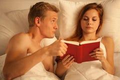 Livre de lecture dans le lit Image stock