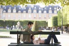 Livre de lecture de couples sur le banc de parc Photos stock