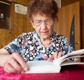 Livre de lecture de dame âgée à la maison Photo libre de droits