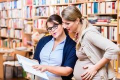 Livre de lecture de deux amis dans la librairie ensemble Images stock