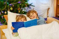 Livre de lecture de deux petit garçons d'enfant de mêmes parents sur Noël Photo stock