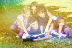 Livre de lecture de famille dans le jardin en été Photographie stock
