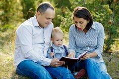 Livre de lecture de famille en parc Image libre de droits