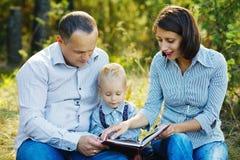 Livre de lecture de famille en parc Photographie stock