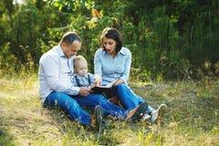 Livre de lecture de famille en parc Images stock