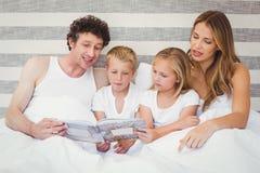 Livre de lecture de famille sur le lit Image stock