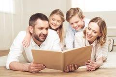 Livre de lecture de famille tout en se trouvant sur le plancher à la maison ensemble photos libres de droits