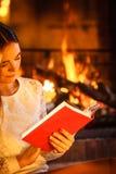 Livre de lecture de femme à la cheminée La maison d'hiver détendent Image stock