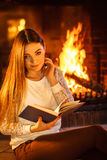 Livre de lecture de femme à la cheminée La maison d'hiver détendent Image libre de droits