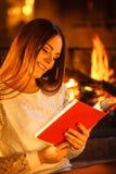 Livre de lecture de femme à la cheminée La maison d'hiver détendent Photographie stock