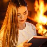 Livre de lecture de femme à la cheminée La maison d'hiver détendent Images stock