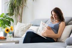 Livre de lecture de femme assez enceinte de jeunes à la maison sur le divan Photo stock