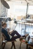 Livre de lecture de femme d'affaires tout en détendant sur la chaise au bureau image stock