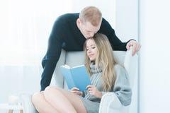 Livre de lecture de femme dans le fauteuil Photo libre de droits