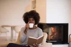 Livre de lecture de femme de couleur devant la cheminée images stock