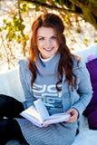 Livre de lecture de femme dehors dans le jour ensoleillé Photo stock