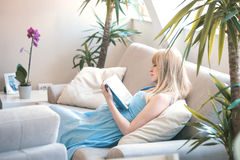 Livre de lecture de femme enceinte en appartement Images stock