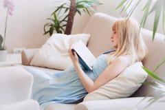 Livre de lecture de femme enceinte en appartement Photo stock