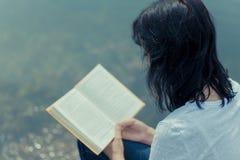 Livre de lecture de femme sur la table de conseil près du lac Photos stock