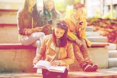 Livre de lecture de fille d'étudiant de lycée dehors Photo libre de droits