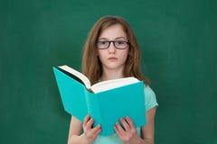 Livre de lecture de fille dans la salle de classe photo libre de droits
