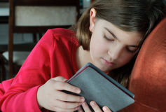 Livre de lecture de fille sur l'E-lecteur Photographie stock