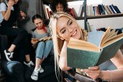 Livre de lecture de fille tandis que ses amis s'asseyant sur la bibliothèque de sofa à la maison Images libres de droits
