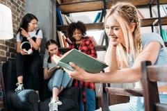 Livre de lecture de fille tandis que ses amis s'asseyant sur la bibliothèque de sofa à la maison Photographie stock libre de droits