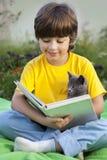Livre de lecture de garçon avec le chaton dans la cour, enfant avec la lecture d'animal familier Image stock