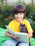 Livre de lecture de garçon avec le chaton dans la cour, enfant avec la lecture d'animal familier Photographie stock