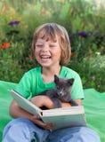 Livre de lecture de garçon avec le chaton dans la cour, enfant avec la lecture d'animal familier Photo libre de droits