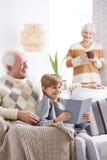 Livre de lecture de garçon avec le grand-père Photos stock