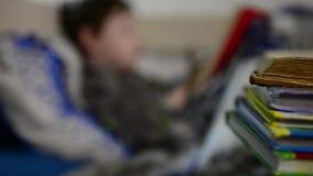 Livre de lecture de garçon dans le lit banque de vidéos