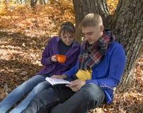Livre de lecture de garçon et de fille et thé potable en parc Photographie stock