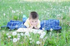 Livre de lecture de garçon se trouvant sur l'estomac extérieur parmi le pissenlit en parc, enfant mignon de sourire, enfants éduc Images stock