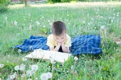 Livre de lecture de garçon se trouvant sur l'estomac extérieur parmi le pissenlit en parc, enfant mignon de sourire, enfants éduc Photos stock