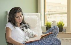 Livre de lecture de jeune femme avec son chien à la maison Images libres de droits
