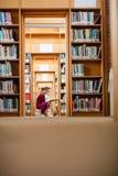 Livre de lecture de jeune femme dans la bibliothèque photographie stock libre de droits