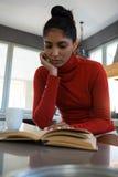 Livre de lecture de jeune femme dans la cuisine photographie stock libre de droits