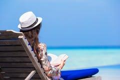 Livre de lecture de jeune femme des vacances d'été à Image stock