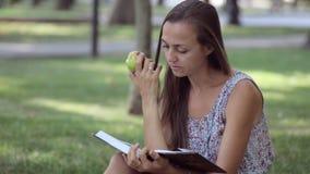 Livre de lecture de jeune femme et pomme de consommation en parc banque de vidéos