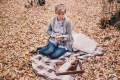 Livre de lecture de jeune femme et thé potable dans une forêt Image stock