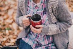 Livre de lecture de jeune femme et thé potable dans une forêt Images stock
