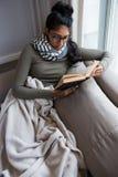 Livre de lecture de jeune femme par la fenêtre sur le sofa image stock