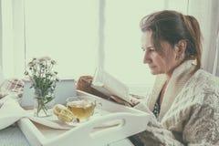 Livre de lecture de jeune femme près de la fenêtre Photo libre de droits
