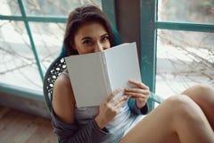 Livre de lecture de jeune femme se reposant près de la fenêtre Photos libres de droits